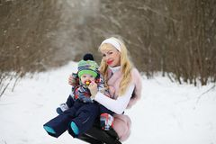 Young mother walks on a winter day with a baby in her arms in th Stock Images