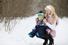 Young mother walks on a winter day with a baby in her arms in th Royalty Free Stock Photo