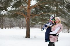 Young mother walks on a winter day with a baby in her arms in th Stock Photos
