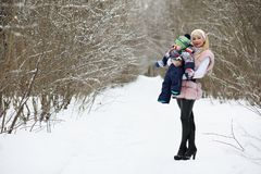 Young mother walks on a winter day with a baby in her arms in th Royalty Free Stock Photography