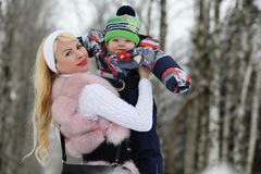 Young mother walks on a winter day with a baby in her arms in th Stock Photo