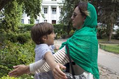 Young mother wearing green shawl and her cute son playing some kind of family game. In the park stock image