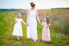 Young mother wearing white dress with two children walking near royalty free stock photography