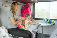 Young mother weave braid of hair daughter on a cot in a train Stock Image
