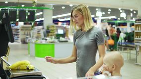 Young mother weighing bananas using self-service electronic scales in the supermarket while her cute child is sitting in stock video