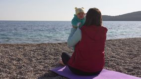 Young mother which sitting on the beach holds her baby in her arms, talks to him stock footage