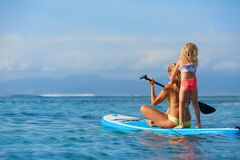 Free Young Mother With Little Clild Paddling On Stand Up Paddleboard Stock Images - 215162124