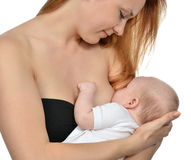 Young mother woman breastfeeding her infant child baby. Young mother women breastfeeding her infant child baby girl lying on her breast and feeding on a whine Royalty Free Stock Image