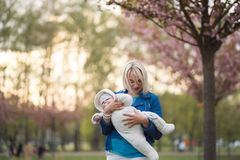 Young mother woman enjoying free time with her baby boy child - Caucasian white child with a parent`s hand visible - stock image