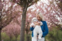 Young mother woman enjoying free time with her baby boy child - Caucasian white child with a parent`s hand visible -. Dressed in white overall with hearts, mom stock photos