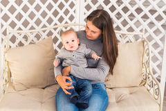 Young mother woman holding and hugging in her arms child baby kid boy smilling laughing Stock Photos