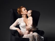 Young mother woman sitting and holding naked her lovely infant child baby. Young mother women sitting and holding naked her lovely infant child baby girl on dark Stock Images