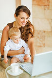 Young mother working with baby on laptop Royalty Free Stock Photography