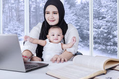 Young mother working with her baby Royalty Free Stock Photos