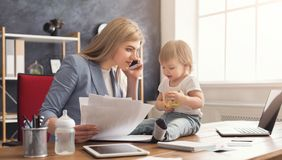 Young mother working and spending time with baby. Happy beautiful business mom talking on smartphone and working with documents in office while her cute baby Royalty Free Stock Photography