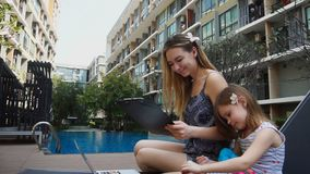 Young mother working on vacations with laptop near swimming pool and little daughter in slow motion. Pretty mother working with documents and laptop in slow stock footage