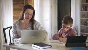 Young mother works with laptop and her son studies online at table during quarantine at home spbd.