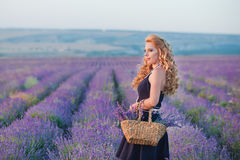 Young mother with young daughter smiling on the field of lavender .Daughter sitting on mother hands.Girl in colorful Royalty Free Stock Image
