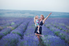 Young mother with young daughter smiling on the field of lavender .Daughter sitting on mother hands.Girl in colorful Stock Image