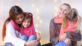 Young mothers with small daughters sit on floor and posing on camera for family photo album. Two beautiful women sit on floor and hold small daughters at hand stock video