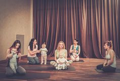 Young mothers and their babies doing yoga exercises on rugs at fitness studio. Stock Photo