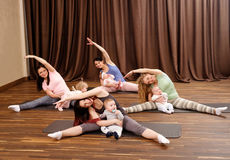 Young mothers and their babies doing yoga exercises on rugs at fitness studio. Stock Photography