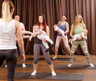 Young mothers and their babies doing yoga exercises on rugs at fitness studio. Royalty Free Stock Photos