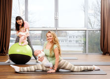 Young mothers and their babies doing yoga exercises on rugs at fitness studio. Stock Image