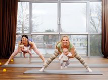 Young mothers and their babies doing yoga exercises on rugs at fitness studio. Stock Images