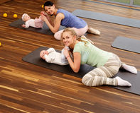 Young mothers and their babies doing yoga exercises on rugs at fitness studio. Stock Photos