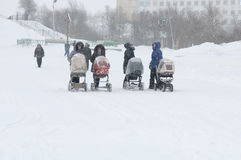 Young mothers are walking with strollers in a snowstorm stock photos