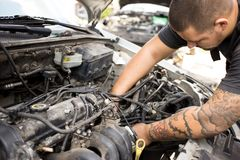 Young mechanic working on a car. Young motivated mechanic working on a car with the hood open royalty free stock image