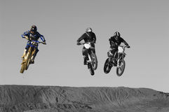 Young motocross racers riding on dirt track Stock Images