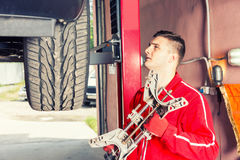 Young motor mechanic holding a piece of equipment in an automoti. Young motor mechanic holding a piece of equipment as he stands alongside the wheel of a car on Stock Photography
