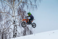 Young motorcycle racer motorcycle flies after jumping over mountain Stock Photo