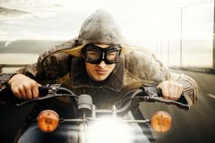Young motorcyclist driving on a road. Young man with hat and goggles vintage look driving on a road royalty free stock photos