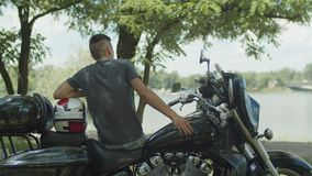 Young motorcyclist having a rest after ride stock footage