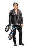 Young motorcyclist holding a small bicycle Stock Images