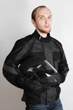 Young Motorcyclist Man Holding Helmet In Studio Royalty Free Stock Image