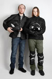 Young motorcyclists man and woman in studio Royalty Free Stock Photos