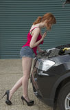 Young motorist looking under the bonnet of her car Stock Image