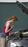 Young motorist using a mobile phone by her car Royalty Free Stock Photos