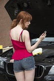 Young motorist using a mobile phone by her car Stock Photos