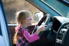 Young motorists. Little girl with pigtails holding the steering wheel - she learns to drive a car Stock Photography
