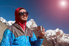 Young Mountain Climber having Refreshment overlooking Mountain Sunny Landscape. Young smiling Mountain Climber drinking Refreshment Drink from Thermo Mug with Royalty Free Stock Image