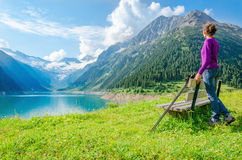 Young mountaineer by mountain lake and high peaks Stock Photos