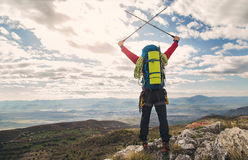 Young mountaineer standing with backpack on top of a mountain Royalty Free Stock Image