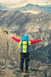 Young mountaineer standing with backpack on top of a mountain Stock Photography