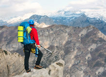 Young mountaineer standing with backpack on top of a mountain Stock Image