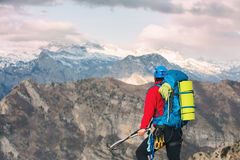 Young mountaineer standing with backpack on top of a mountain Royalty Free Stock Photography